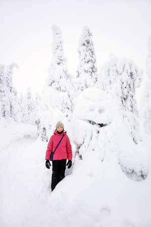 Cute pre-teen girl next to funny snow ghost tree in winter forest in Lapland Finland 免版税图像