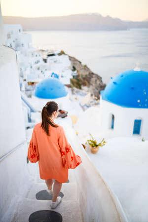 Beautiful girl on summer vacation enjoying breathtaking sunrise view of blue-domed church in Oia village on Santorini island Greece 免版税图像