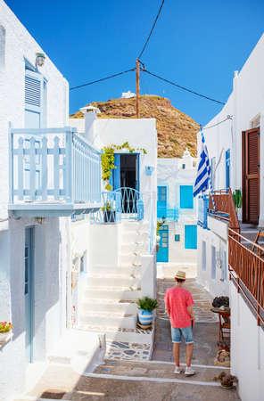 Back view of teenage boy enjoying walk around old traditional Greek cycladic village of Plaka on Milos island 免版税图像