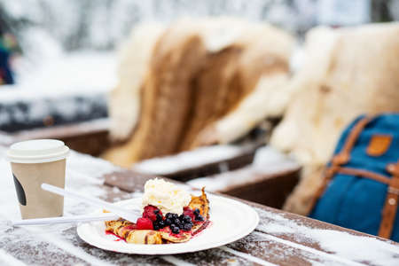 Delicious crepes with berries and whipped cream served outdoors on snowy winter day