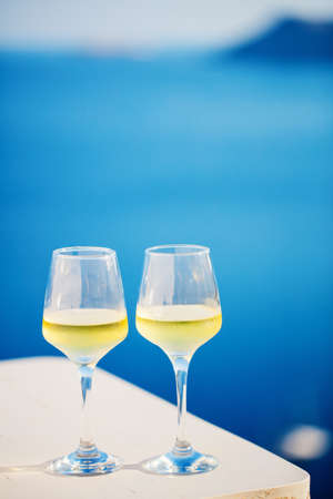 Two glasses of white wine over sea view background