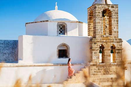 Young girl exploring traditional whitewashed Greek Orthodox church in Plaka village on Milos island