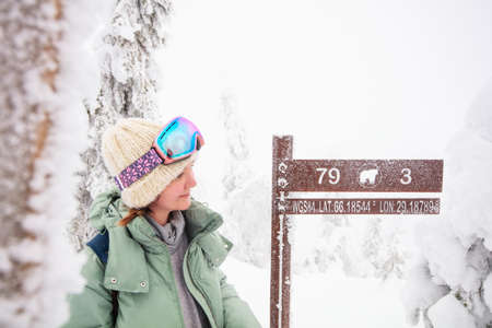 Young beautiful woman next to signpost on Valtavaara winter hiking trail in snow covered forest in Lapland Finland 免版税图像