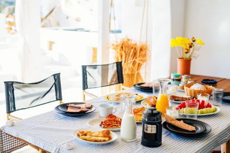 Delicious breakfast served at outdoor terrace of luxury villa 免版税图像