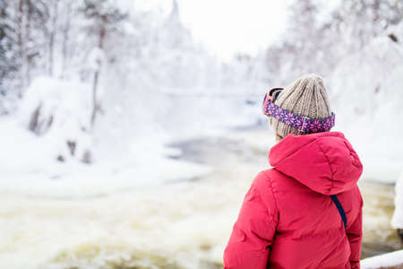 Back view of pre-teen girl enjoying breathtaking view of winter landscape in Oulanka National Park in Lapland Finland
