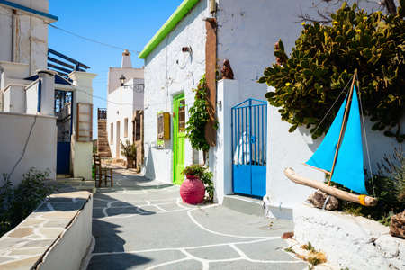 Beautiful street in old traditional Greek cycladic village of Plaka with white houses and colorful doors on Milos Island