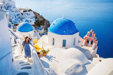 Beautiful girl on summer vacation enjoying breathtaking view of blue-domed church in Oia village on Santorini island Greece