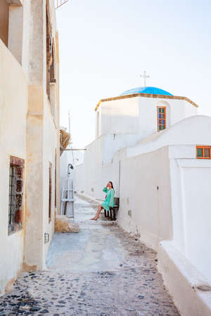 Young woman on summer vacation sitting on bench next to blue domed church in Pyrgos village on Santorini island Greece 免版税图像