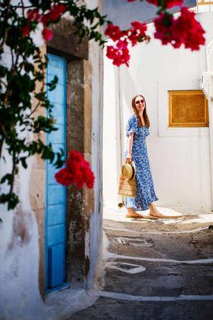 Young beautiful woman walking along quiet street in Plaka village on Milos island in Greece