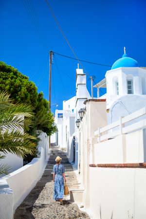 Back view of young woman on summer vacation walking near blue domed church in Pyrgos village on Santorini island Greece