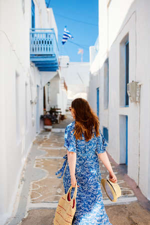 Back view of young beautiful woman walking along quiet street in Pyrgos village on Santorini island in Greece 免版税图像
