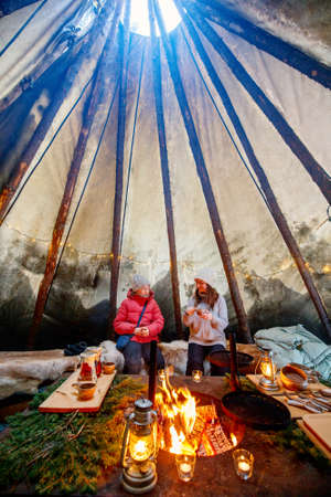 Family of mother and daughter relaxing with cup of hot drink next to open fire in atmospheric Lappish hut