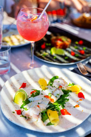 Close up of gourmet fresh fish carpaccio served for lunch in outdoor restaurant