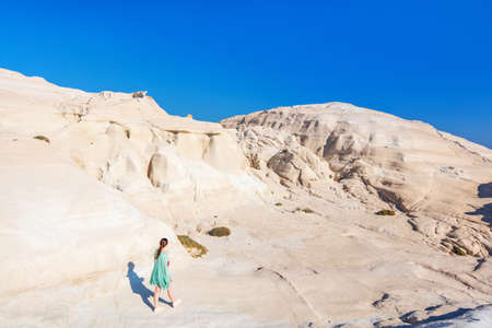 Attractive young woman walking on the lunar like landscape of Sarakiniko volcanic rock formations on island of Milos in Greece