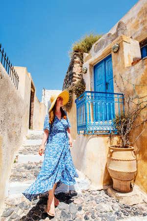 Young beautiful woman walking along quiet street in Pyrgos village on Santorini island in Greece 免版税图像