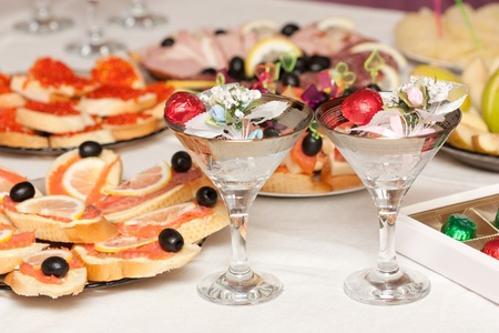 Close up of a festive table with sweets, sandwiches and wine glasses photo