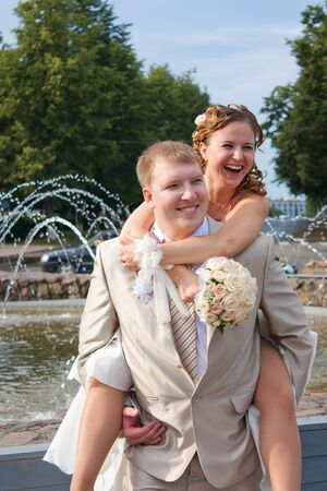 The bride sits on a back at the cheerful groom and laughs photo