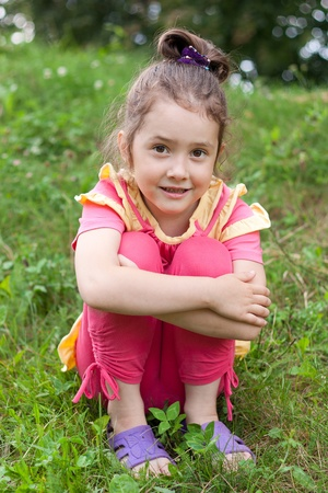 hugging knees: The little girl sits on a grass having drawn in knees