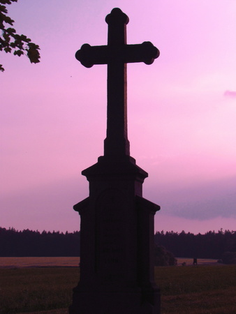 Silhouette of a cross on a background of sky with red clouds, evening twilight