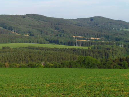 Rural hilly landscape, country with green meadow in summer, forest, Czech republic Фото со стока