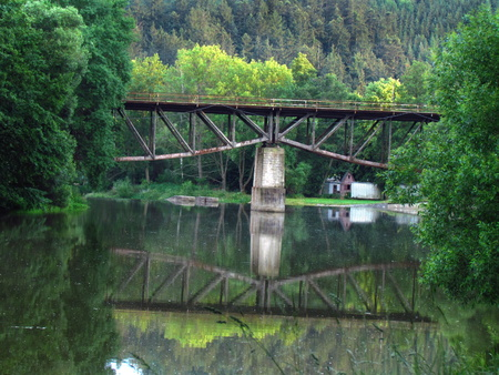 Old railway bridge over the river, mirroring in the water