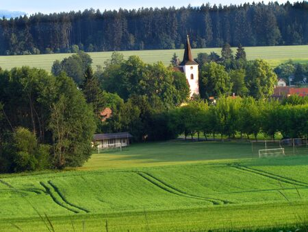 Summer view of the village in the hilly countryside, church tower, football pitch