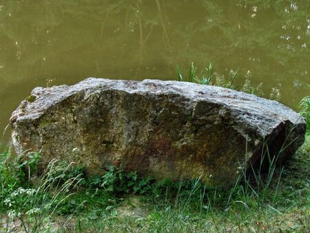 Big stone on the grass by the river Фото со стока