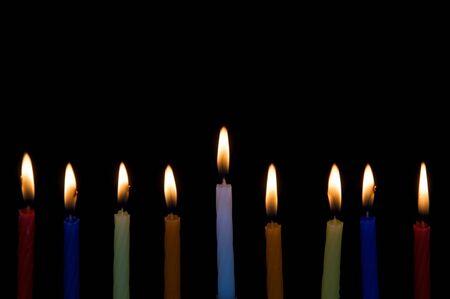 hanukah: 9 Hanukah Candles burn, isolated on black Stock Photo