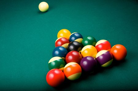 Billiard balls are racked in a triangle, waiting to be broken by the cue ball. Shallow depth of field.