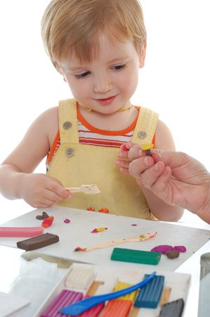 little boy playing with many-coroled plasticine photo