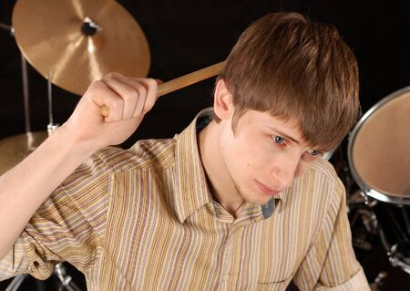 percussionist: Young musician playing drums isolated on black. Stock Photo