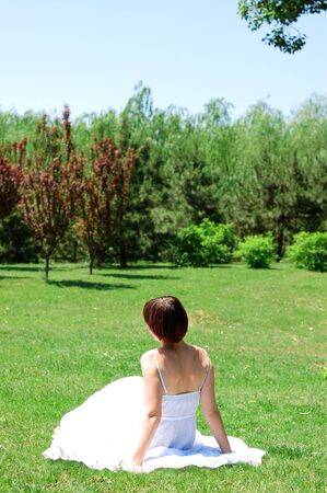 Beautiful young woman have a rest on sunny lawn. photo