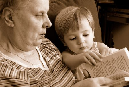 grandmother read the book for her grandson. sepia photo