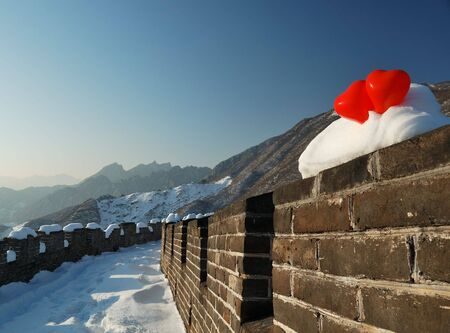 two red balloon in the form of a heart on Great wall in snow photo