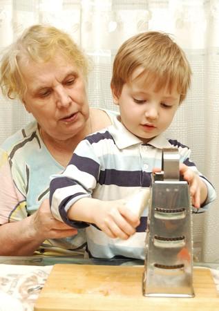 elderly woman with her grandson grate radish photo
