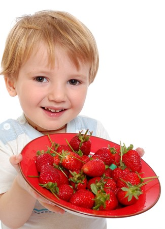 little cute boy show strawberries on a white background photo