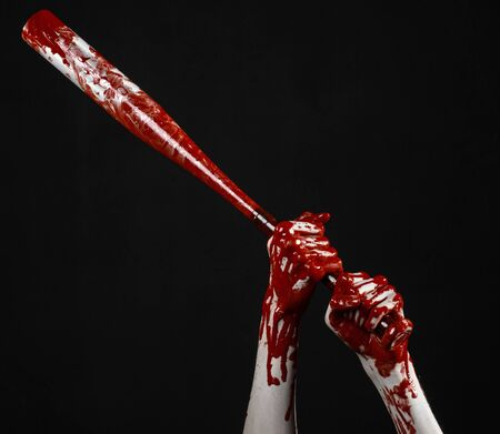 blood sport: bloody hand holding a baseball bat, a bloody baseball bat, bat, blood sport, killer, zombies, halloween theme, isolated, black background studio Stock Photo