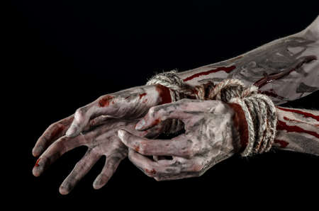 diabolic: Hands bound,bloody hands, mud, rope, on a black background, isolated, kidnapping, zombie, demon studio Stock Photo