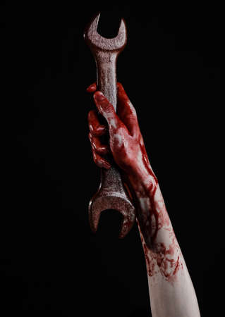 carnage: bloody hand holding a big wrench, bloody wrench, big key, bloody theme, halloween theme, crazy mechanic, murderer, psycho, violence, zombies, black background, isolated, revolution studio Stock Photo