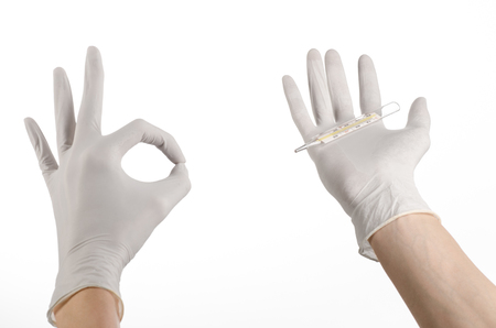 malaise: Medical theme: doctors hand in white gloves holding a thermometer to measure the temperature of the patient on a white background studio