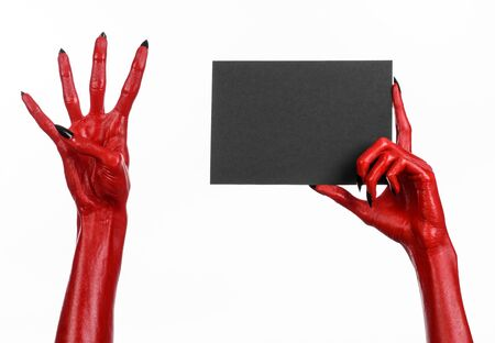 satan: Halloween theme: Red devil hand with black nails holding a blank black card on a white background studio