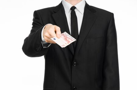 10 fingers: Money and business theme: a man in a black suit holding a bill of 10 euros and shows a hand gesture on an isolated white background Stock Photo