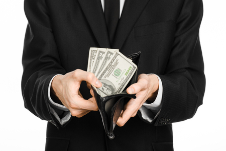 show bill: Money and business theme: a man in a black suit holding a purse with paper money dollars isolated on white background Foto de archivo