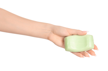 Hygiene and health care topic: a woman's hand holding a green bar of soap isolated on white background