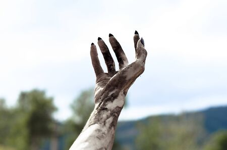 rising dead: Horror and Halloween theme: Terrible zombie hands dirty with black nails reach for the sky, walking dead apocalypse, first-person view studio