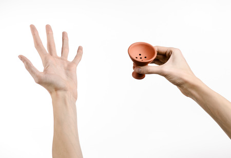 glycerol: Hookah topic: Bartender holding a clay bowl for tobacco on a white background isolated