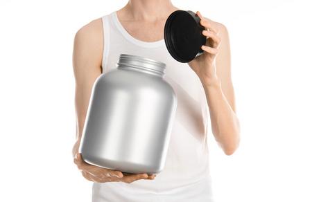 thin man: Culturismo y deportes tema: un hombre delgado en una camiseta blanca y pantalones vaqueros sosteniendo un frasco de pl�stico con una prote�na aislada en un fondo blanco Foto de archivo