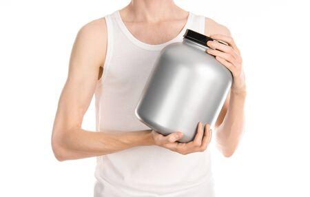 hombre flaco: Culturismo y deportes tema: un hombre delgado en una camiseta blanca y pantalones vaqueros sosteniendo un frasco de pl�stico con una prote�na aislada en un fondo blanco Foto de archivo