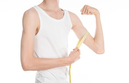 Bodybuilding and Sports theme: a thin man in a white T-shirt and jeans with measuring tape isolated on a white background