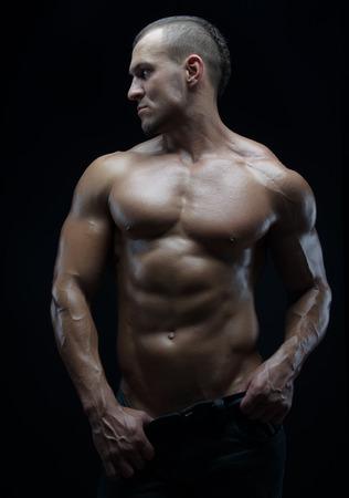 hombre desnudo: Fisicoculturista y el tema de la tira: hermosa con los m�sculos bombeados hombre desnudo posando en el estudio sobre un fondo oscuro del arte Foto de archivo